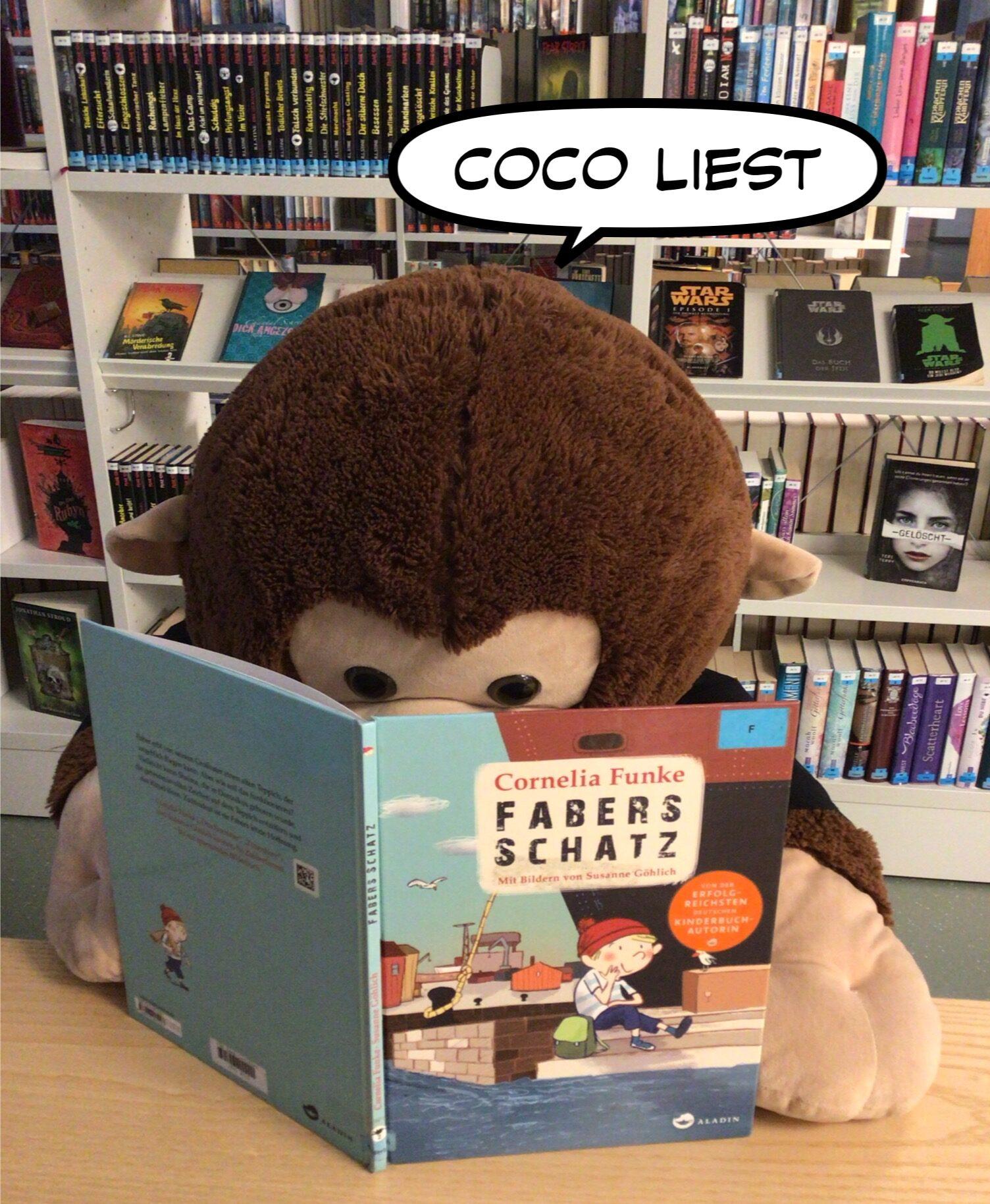 Coco liest ein Bilderbuch in der Mediathek